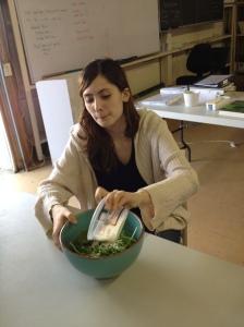 student mixing arugula and Parmigiano-Reggiano