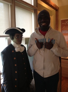 another student posing with Benjamin Banneker's statue